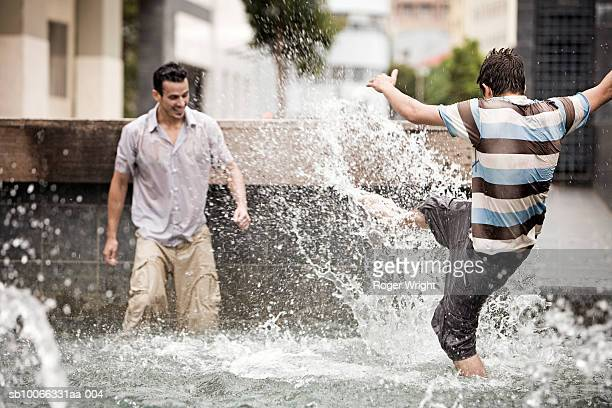 Two men splashing in fountain