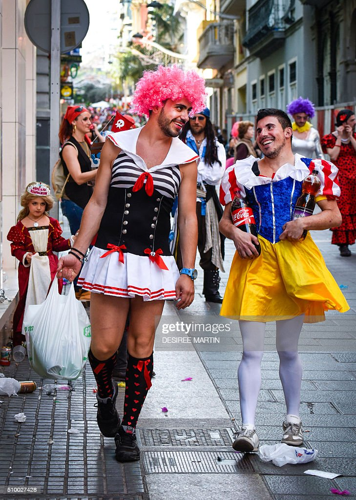 Two men sport their costumes as they participate in a street carnival in Santa Cruz de Tenerife on the Spanish Canary island of Tenerife on February 13, 2016. The over a month long carnival sees orchestras playing Caribbean and Brazilian rhythms throughout the festivities that range from elections for the Carnival Queen, children and adult murgas (satirical street bands), comparsas (dance groups) to performances on the streets. / AFP / DESIREE MARTIN
