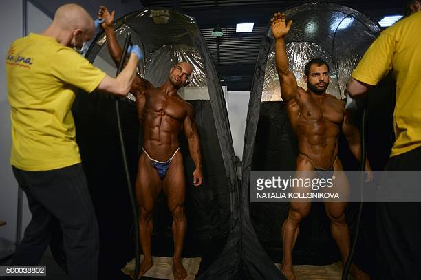 Two men spray posing oil on participants prior to compete in the Bodybuilding Prow Power Show on December 5 2015 in Moscow / AFP / NATALIA KOLESNIKOVA