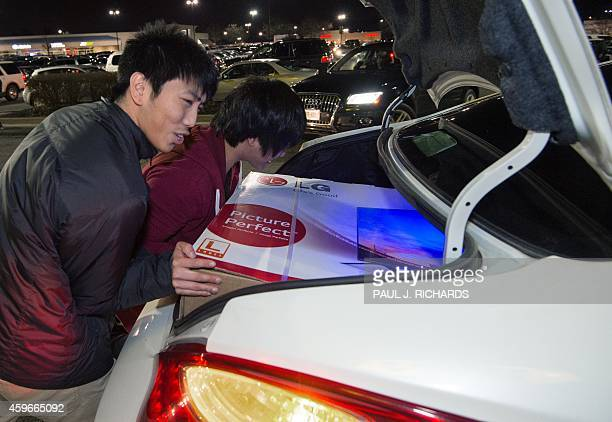 Two men squeeze their newly purchased 55' screen TV into their car outside the Best Buy during the Black Friday doorbuster sale that started on...