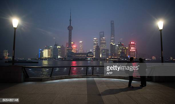 TOPSHOT Two men stand at the bund near the Huangpu river across the Pudong New Financial district in Shanghai on January 18 2016 China recorded its...