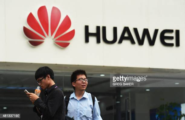 Two men stand in front of a Huawei store in Beijing on July 20 2015 Chinese telecoms equipment giant Huawei said on July 20 that revenue surged 30...