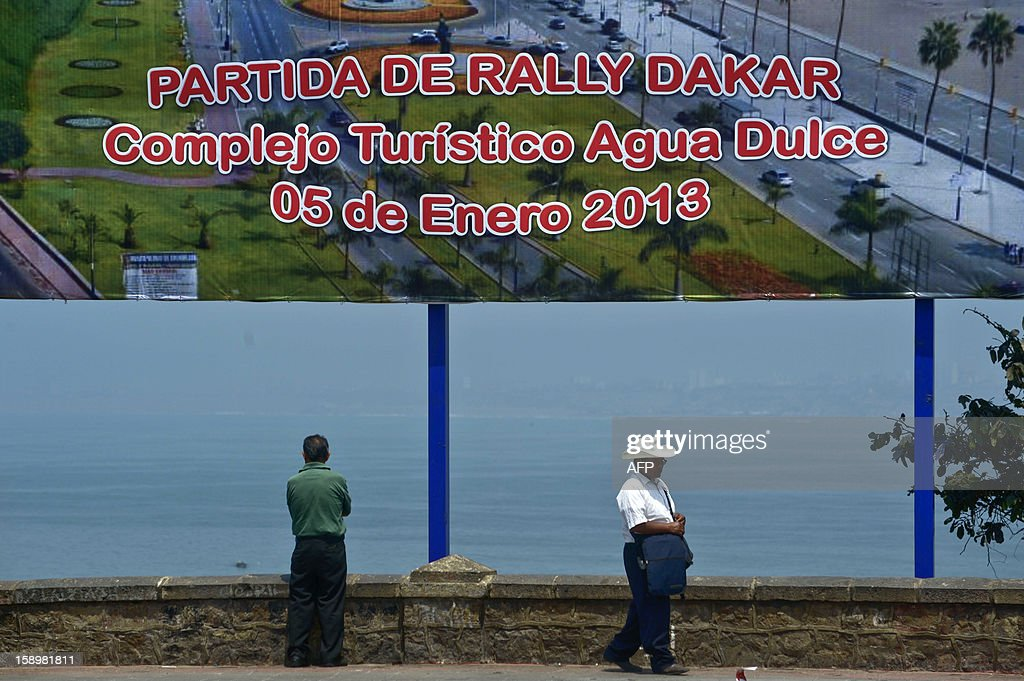 Two men stand in front of a sign advertising the 2013 Dakar Rally in Lima on January 4, 2013. This year the rally will thunder through Peru, Argentina and Chile from January 5 to 20. AFP PHOTO /ERNESTO BENAVIDES