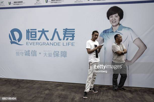 Two men stand in front of an advertisement for Evergrande Life Insurance Co inside the Hainan Boao Lecheng InternationalMedicalTourismPilotZone...