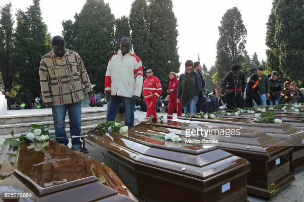 Two men stand in front of the coffins during the funeral of the 28 migrant women who died in a shipwreck as they sought to reach Italy