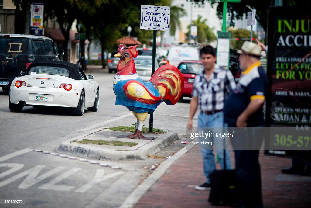 Two men stand near a sign welcoming people to Calle 8, or Eighth Street, in the Little Havana district of Miami, Florida, U.S., on Wednesday, Feb. 20, 2013. U.S. exports in the travel and tourism sector reached $168.1 billion in 2012, up 10.1 percent from the year-ago level of $152.7 billion, according to data released Feb. 22 by the Commerce Department's International Trade Administration. Photographer: Ty Wright/Bloomberg via Getty Images