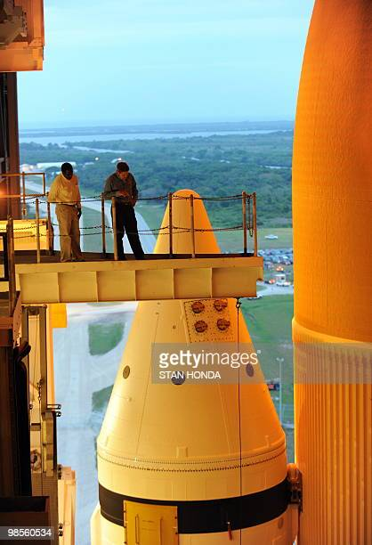 Two men stand near one of the solid rocket boosters and the external fuel tank while the space shuttle Atlantis stands ready in the Vehicle Assembly...