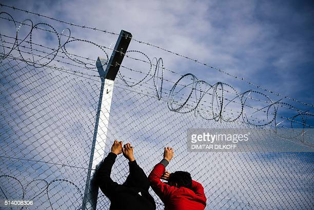 TOPSHOT Two men stand next to a razortopped fence close to the gate at the GreekMacedonian border near the Greek village of Idomeni on March 6 where...