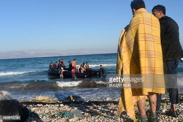 Two men stand on a beach as migrants and refugees begin to board a dinghy to travel to the Greek island of Chios from Cesme in the Turkish province...