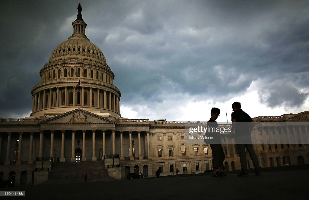 Two men stand on the plaza of the US Capitol Building as storm clouds fill the sky June 13 2013 in Washington DC Potentially damaging storms are...