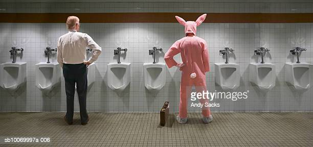 Two men standing at urinal, one in rabbit costume, rear view (digital composite)