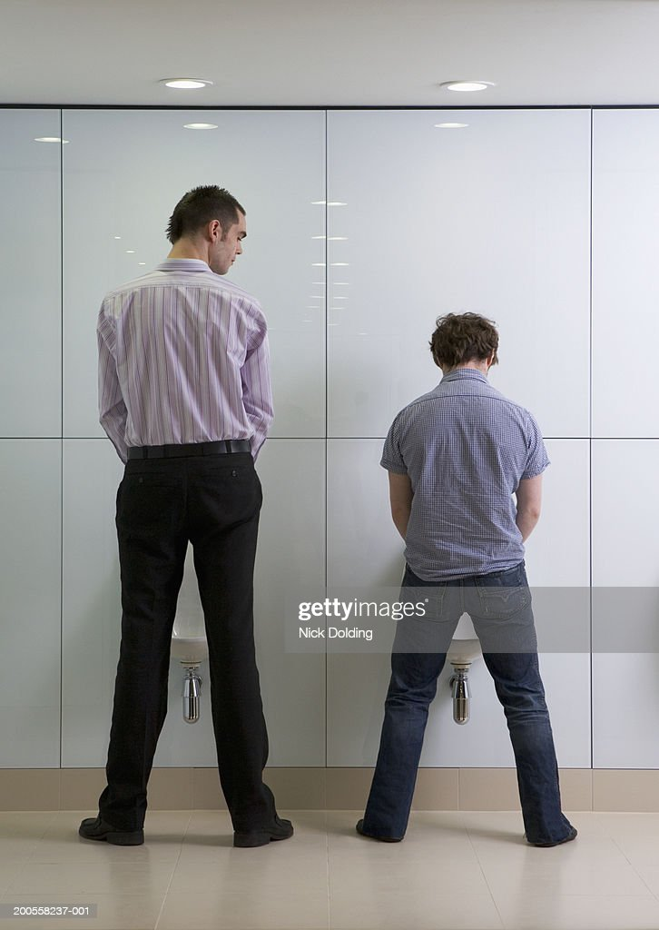 Two men standing at urinal, rear view