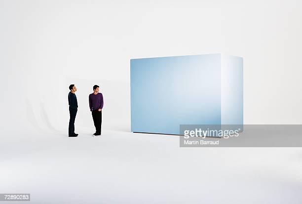 Two men standing beside empty giant box