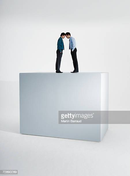 Two men standing head to head on top of giant box