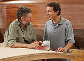 Two men standing in boat building workshop, smiling, side view