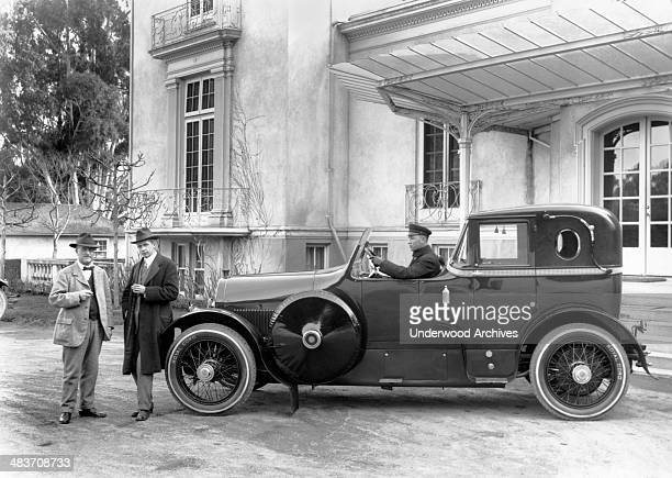 Two men standing in front of an open cab limousine mid 1920s