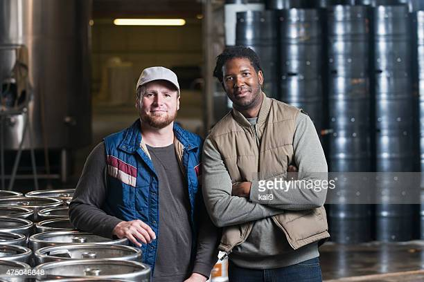 Two men standing in storage warehouse with steel drums
