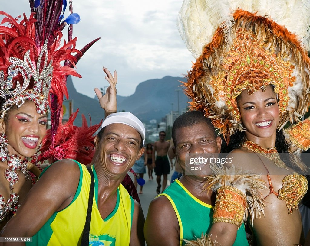 Two men standing next to  female carnival dancers, smiling, portrait : Stock Photo