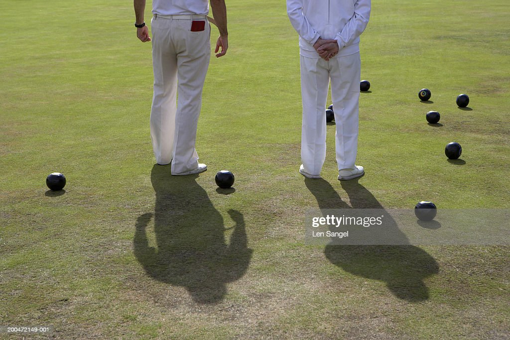 Two men standing on bowling green, rear view, low section