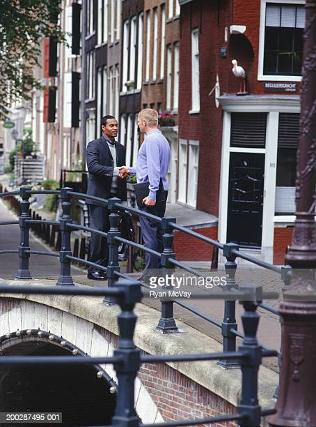 Two men standing on street, shaking hands, Amsterdam, Holland