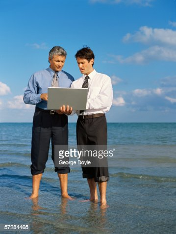 Two men standing on the beach and using a laptop