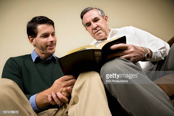 Two men studying the Bible together on a couch