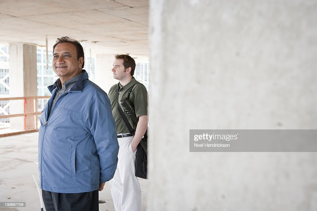 Two men take a look around a construction site : Stock Photo