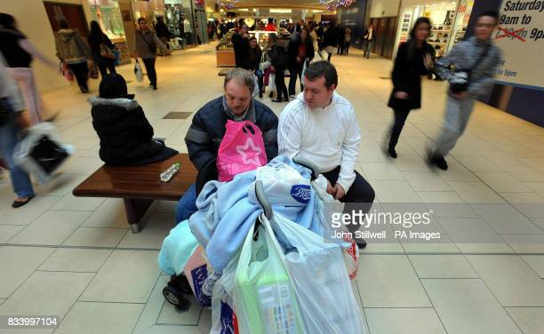 Two men take a rest in Lakeside shopping centre in Essex where shoppers were out in force with less than two weeks before the Christmas holiday