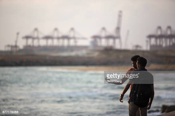 Two men take a selfie photograph at the sea front of Galle Face Green as the construction site of the Colombo Port City development stands in the...