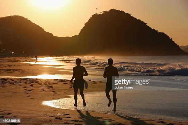 Two men take an early morning jog along Copacabana beach on June 9 2014 in Rio de Janeiro Brazil