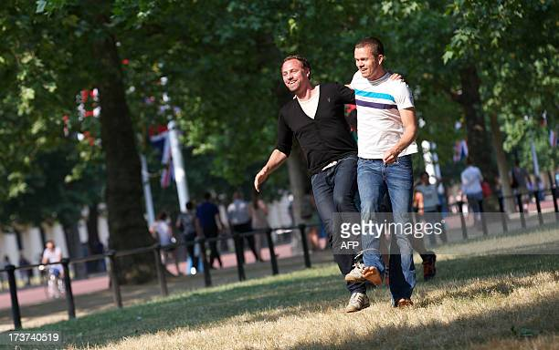Two men take part in a three legged race during a sunny day at St James Park in central London on July 17 2013 British authorities issued a heatwave...
