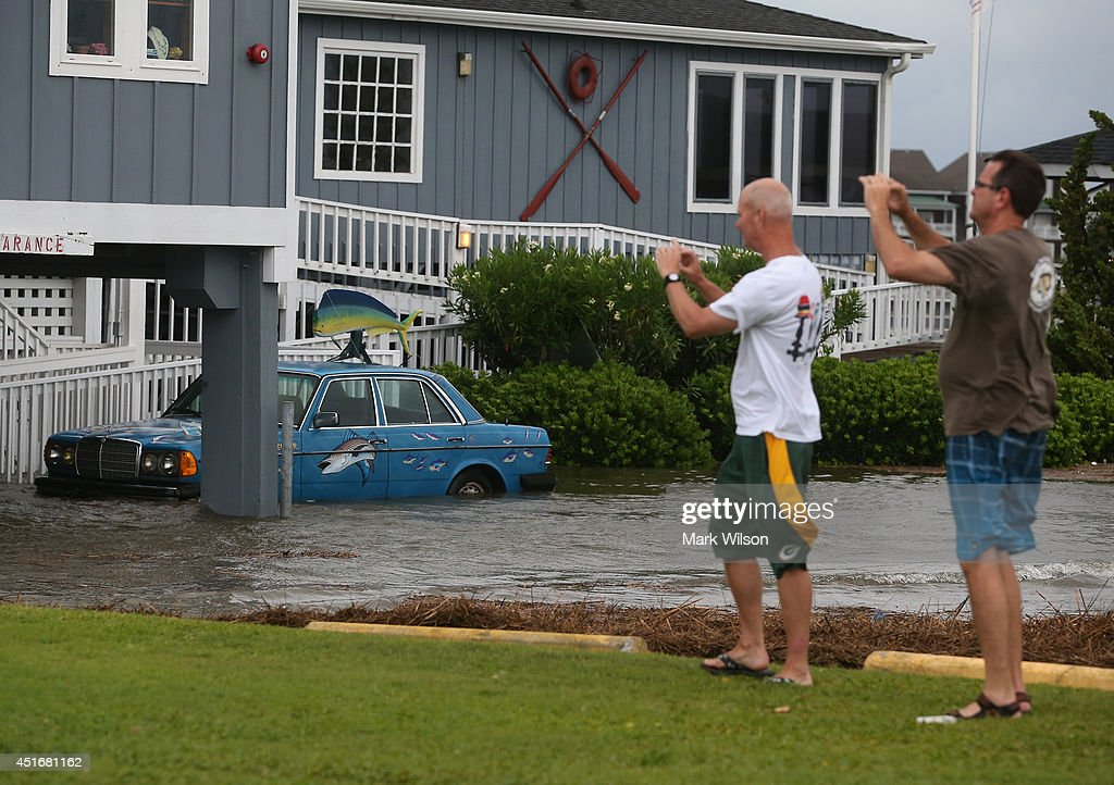 Two men take pictures of the flooding at a restaurant on Hwy 64 that is flooded by Hurricane Arthur, July 4, 2014 in Nags Head, North Carolina. Hurricane Arthur hit North Carolina's Outer Banks overnight causing wide spead power outages and minimal flooding and damage.