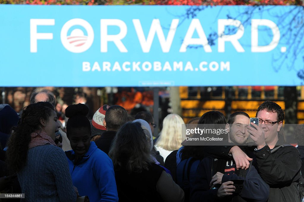 Two men take their picture prior to President Barack Obama speaking at an event at Veteran's Memorial Park October 18, 2012 in Manchester, New Hampshire. President Obama continues to campaign in swing states with just under three weeks left till Election Day.