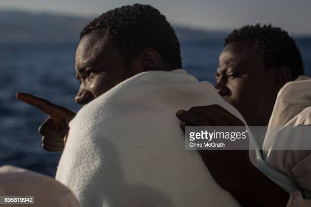 Two men talk about Italy as they arrive in port on the Migrant Offshore Aid Station Phoenix vessel on June 12 2017 in Reggio Calabria Italy An...