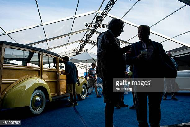 Two men talk as they stand in front of a 1939 Ford Motor Co V8 Model 91A Deluxe Station Wagon during the Gooding and Company auction at the 2015...