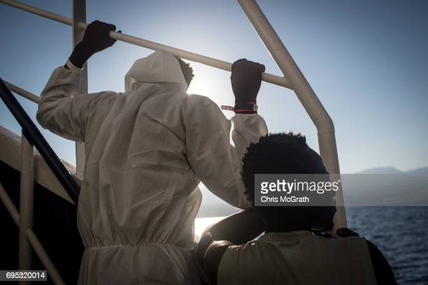 Two men talk look out at Italy as they arrive in port on the Migrant Offshore Aid Station Phoenix vessel on June 12 2017 in Reggio Calabria Italy An...
