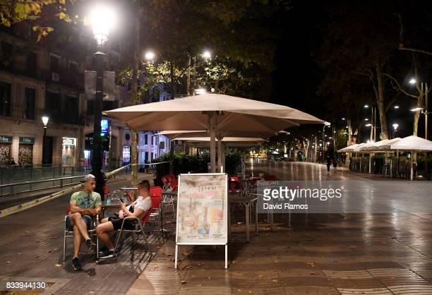 Two men talk to each other in an empty terrace in the Las Ramblas area following a terrorist attack earlier today on August 17 2017 in Barcelona...