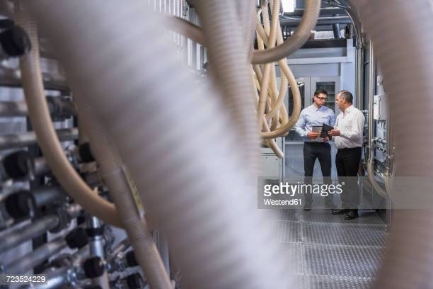 Two men talking about the system in factory