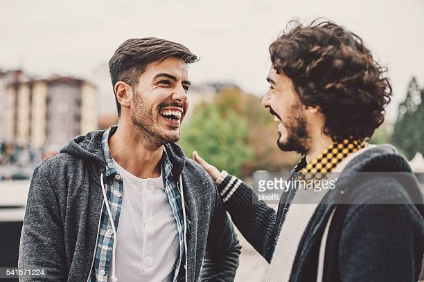 Two men talking and smiling on the street