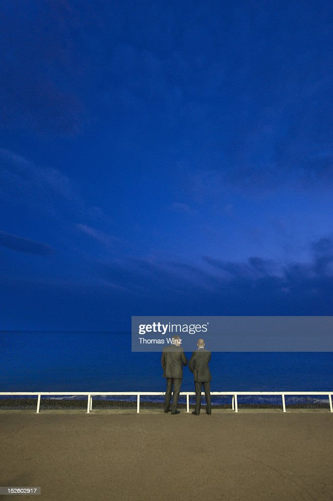 Two men talking at dusk along promenade : Stock Photo