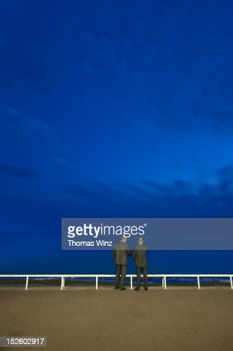 Two men talking at dusk along promenade : Photo