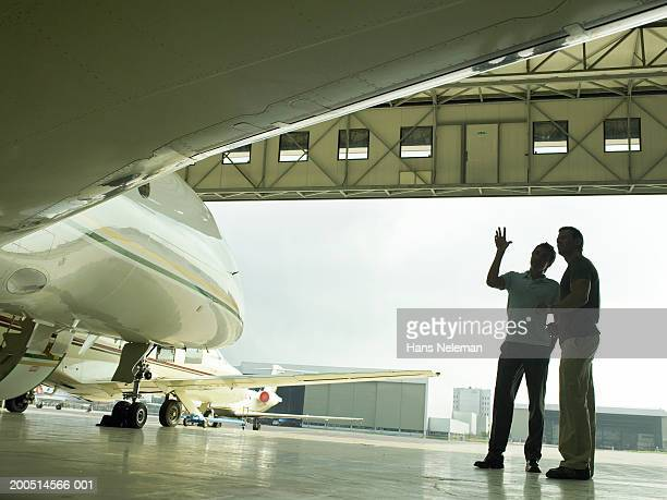 Two men talking by private plane in hangar, low angle view