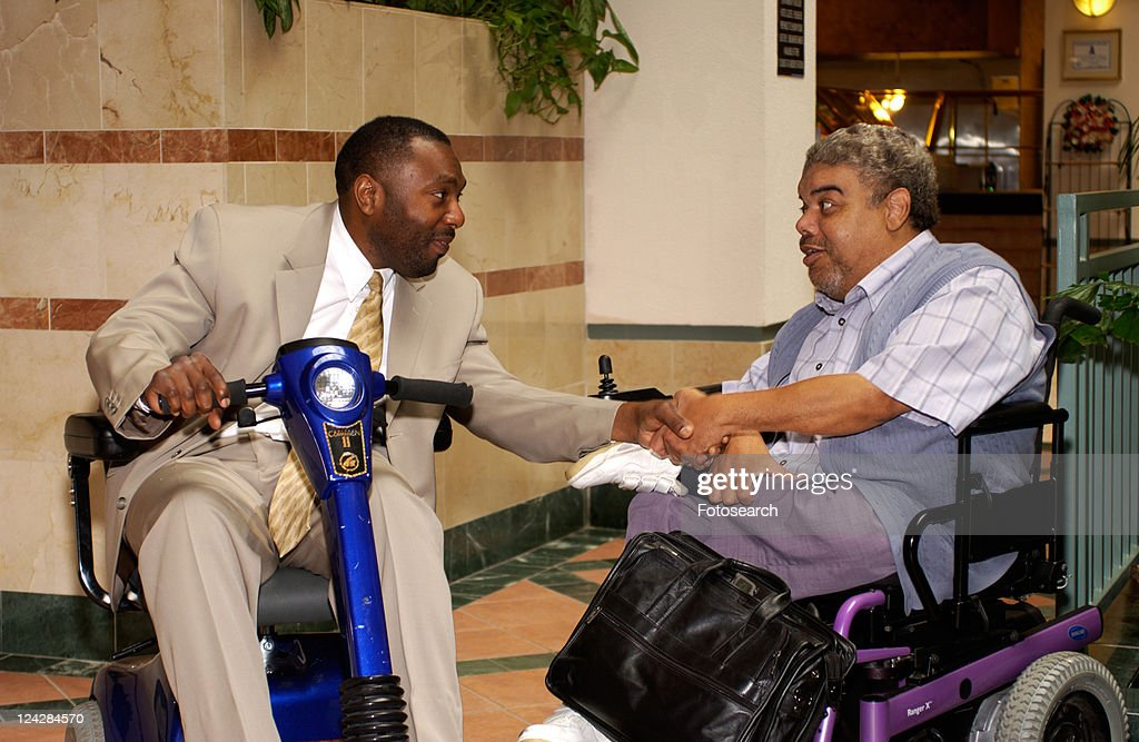 Two men talking during a break at a Disability Activist Conference. : Stock Photo