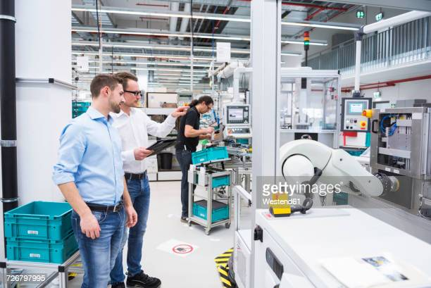 Two men talking in factory shop floor with man in background working