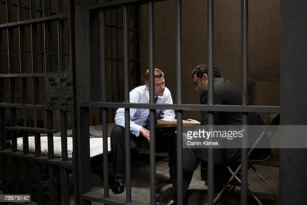 Two men talking in prison cell, side view