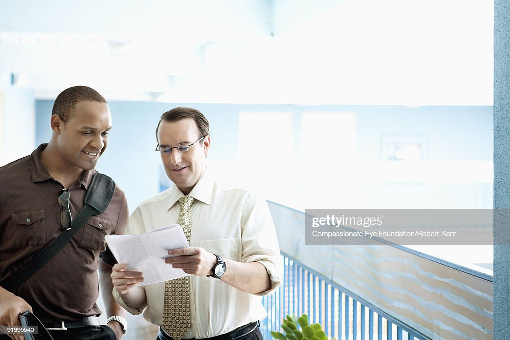 two men talking over a document