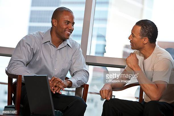 two men talking with computer on table