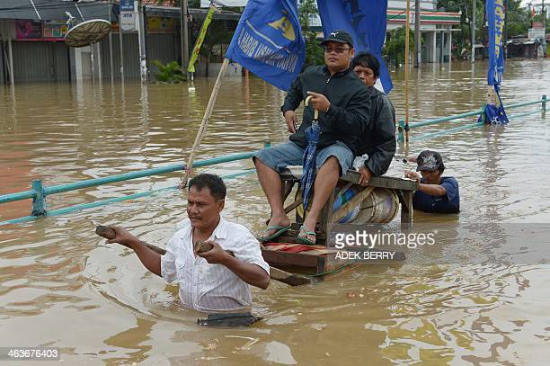 Two men taxi a couple with a simple cart to gain money after an area was hit by floods in Jakarta on January 19 2014 The death toll in days of floods...
