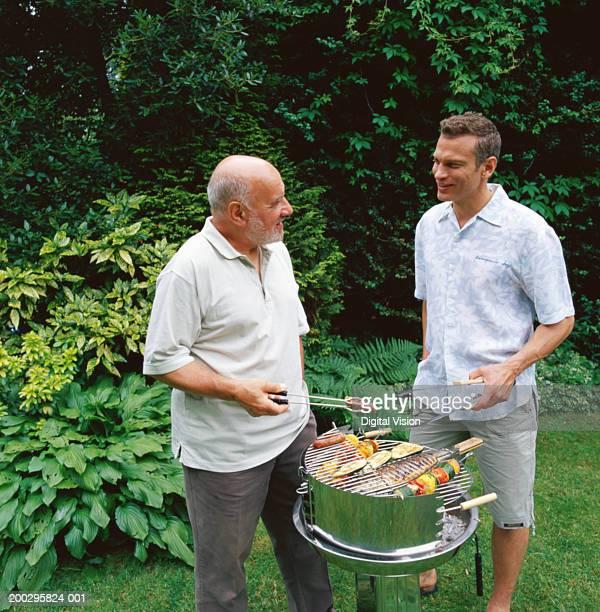 Two men tending barbecue, holding utensils
