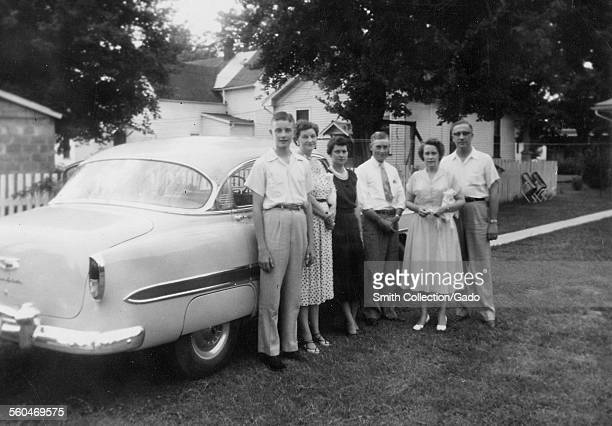 Two men three women and a teenage boy standing in front of a car on the street posing for a picture Evansville Indiana 1948